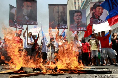 Protesters, mostly workers, burn a mural depicting U.S. President Barack Obama and Philippine President Benigno Aquino III after being blocked by police from getting closer to the U.S. Embassy in Manila to mark International Labor Day Wednesday May 1, 2013 in Manila, Philippines.