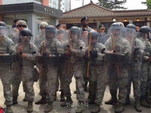 U.S. Army bravely defending Osan Airforce Base from bloodthirsty legions of hostile civilians delivering a letter of petition to Osan's commanding officer.