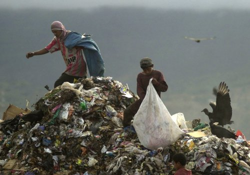 Two men look for scraps at a garbage dump in Tegucigalpa, Honduras, Saturday, Jan. 26, 2002. In Honduras poverty affects 81.1% of the population which is 6.7 million of which 2.6 million have to get by with only one dollar per day while the basic cost of living is $ 7 per day. (AP Photo/Esteban Felix)